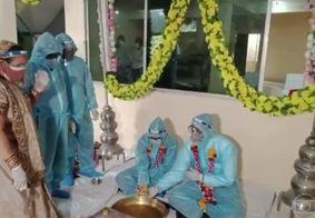 Noivos se casam com roupa de proteção contra o novo coronavírus