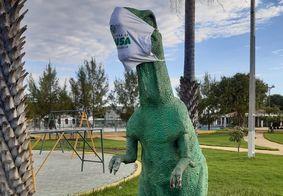 Esculturas de dinossauros ganham máscaras para conscientização da população
